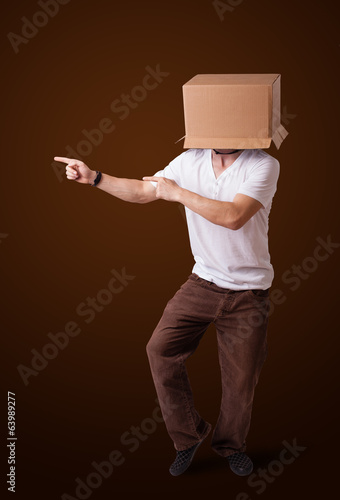 Young man gesturing with a cardboard box on his head