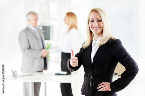 Happy young businesswoman showing thumbs up in the office.