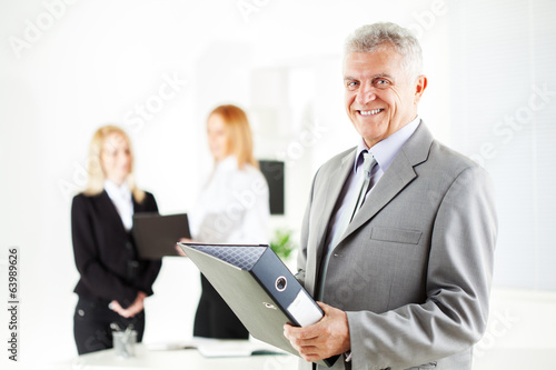 Senior businessman with documents standing in the office