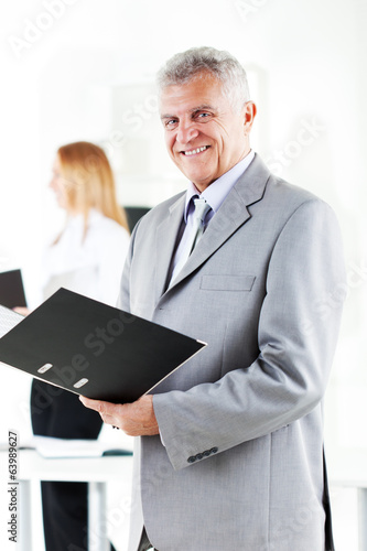 Happy senior businessman with folder standing in the office.