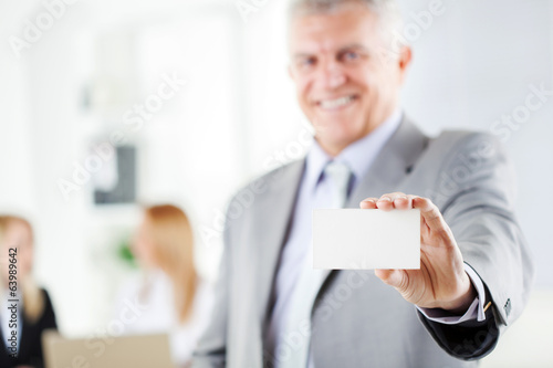 Happy senior businessman holding Blank business card