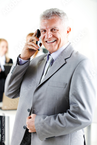 Happy senior businessman talking on mobile phone