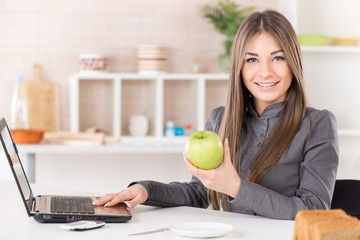 Businesswoman in the kitchen with apple and laptop