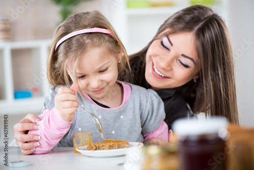 Mother and daughter preparing breakfast.