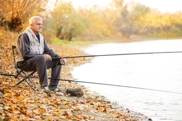 Senior men fishing by the lake.