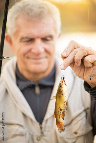 Senior Fisherman holding fish on the hook.