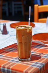 Glass of ice cold frappe coffee with a drinking straw