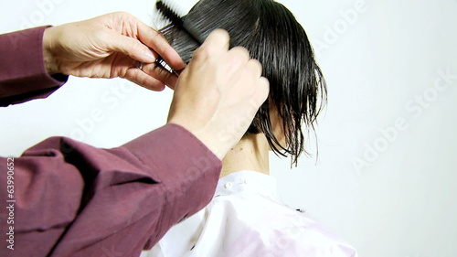 Professional hair stylist cutting hair short