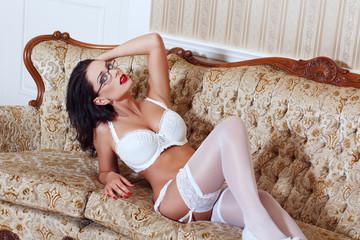 Sexy woman posing on sofa in white stockings
