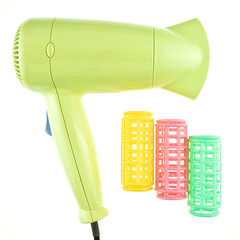Old green hairdryer and colorful curler isolated