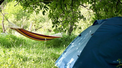 Camping equipment: touristic Tent and Hammock between the trees