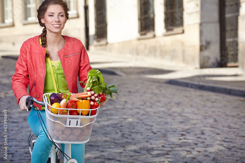 Pretty spring  woman with bicycle and groceries in old town stre