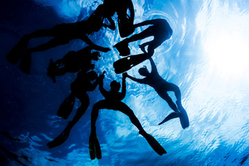 People snorkeling and hold together
