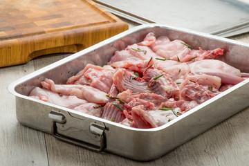 Pezzi di coniglio crudo nella teglia per essere cucinato