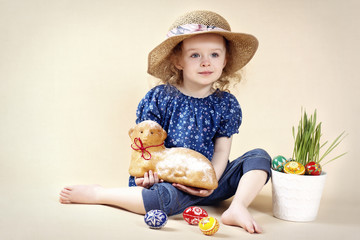 Little girl with Easter lamb and easter eggs