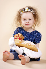 Little girl with oven mitts holding Easter lamb