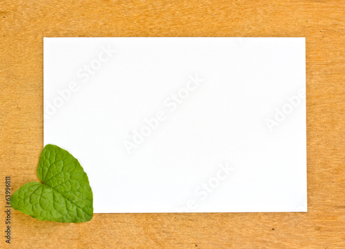 blank pape and leaf on wooden bords