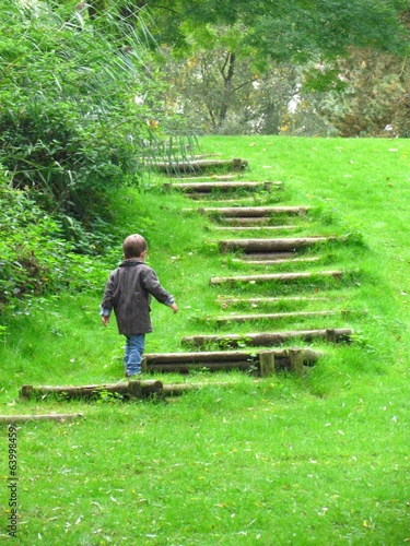 boy ascending wooden stairs