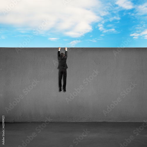 Trying to climb over wall with blue sky background