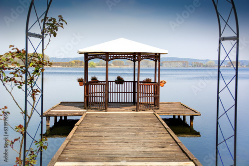 Wooden gazebo on dock over peaceful lake