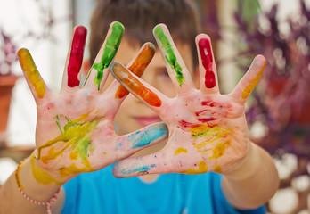 Niño con manos pintados de distintos colores