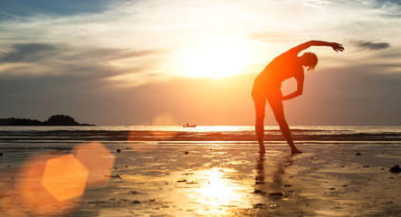 Woman silhouette exercise on the beach at sunset.