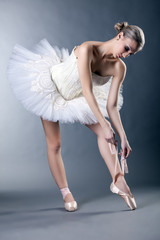 Beautiful young ballerina tying pointe in studio