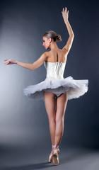 Rear view of graceful young ballerina dancing