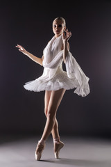 Adorable contemporary ballerina dancing in studio