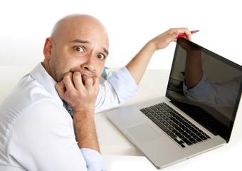 bald worried latin business man biting nails on computer