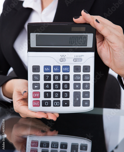 Businesswoman Holding Calculator At Desk