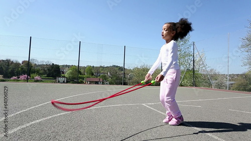 Young girl skipping with a jump rope