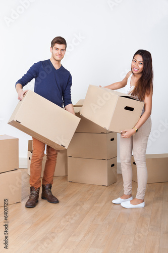 Young Couple Carrying Cardboard Boxes At New Home