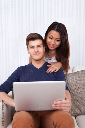 Man Using Laptop With Woman In Living Room