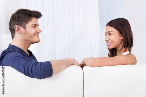 Couple Looking At Each Other On Sofa