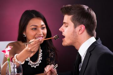 Woman Feeding Man In Restaurant