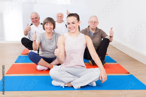Confident Trainer With Senior Customers At Gym