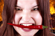 girl having fun, holding red hot chilly pepper in mouth.