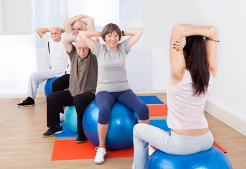 Trainer Training Customers Stretching On Fitness Balls