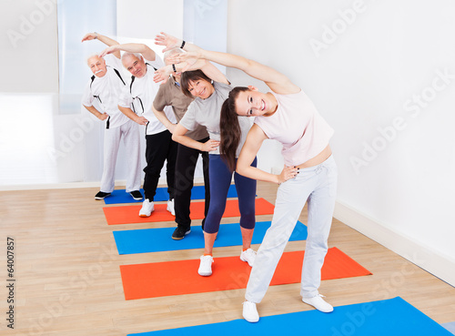 Trainer And Customers Doing Stretching Exercise