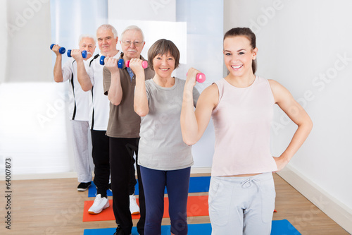 Trainer And Customers Exercising With Dumbbells