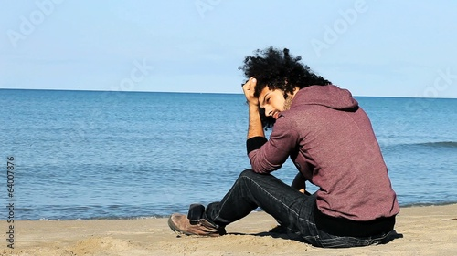 Handsome italian man sitting on beach thinking