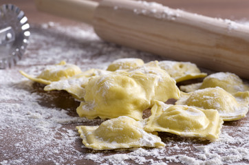 homemade uncooked ravioli with a roller on wooden table