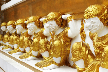 golden giants  statue  on the base  wall  pagoda in  temple