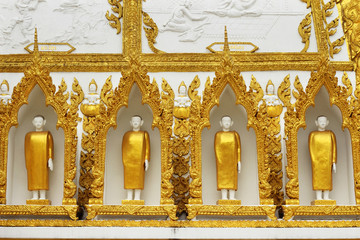 golden buddha statue standing on the wall  temple