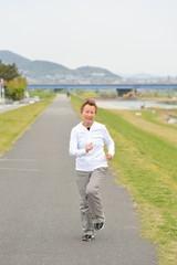 ランニングコースを健康のために走る高齢の日本人女性