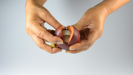 A hands paring mangosteen isolated on white