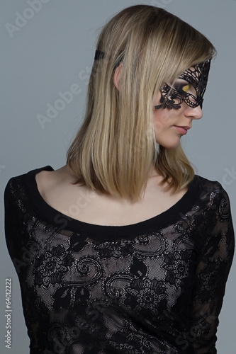 Girl in black lace mask on gray background