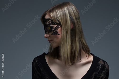 Girl in black lace mask looking at her shoulder