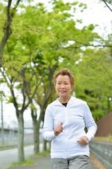 新緑の木々が植えてある歩道を健康のためにジョギングしている高齢のアジア人女性